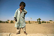 An Afghan boy rubs his eyes as a convoy of the 2-87 Unit of 3rd Brigade Tenth Mountain Division, 1-102 Infantry, drives pass his village in Ghazni, Afghanistan, Saturday, Sept. 30, 2006. The US troops began conducting Operation Mountain Fury since Sept. 12, 2006, and the platoons from Ghazni FOB had been on a mission, killing at least 17 Taliban fighters in Andar district. Now during the times of Ramadan, the Holy Month for Muslims, the Taliban activities have been dwindled down in the region as units from 102nd Inf. conduct mild operations of Mt. Fury such as village assessments and humanitarian drop-offs, the US troops are still exposed to a danger of hidden combat by the remaining Taliban fighters in this area. Members of 2-87 Unit, comprised with 41 personnel from all over the US aged from 19 to 35. The 102nd Inf., dated back to the Civil War time, from New Haven, Conn., had arrived in Ghazni in April this year and will stay here for one year until it is replaced by another inf. of reservists next April.