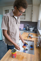 Teenage boy rinsing out tins at kitchen sink before putting them out for recycling,