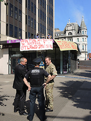 © Licensed to London News Pictures. 25/07/2014. Cardiff, UK. A group of 3 protesters scaled the roof of the armed Forces recruitment office in protest of current recruitment policy and UK involvement in NATO. The group, from Newport,where the NATO summit will be held in September, is part of the Anarchist Action Network. Beyond that they declined to give details. Police are monitoring the situation and have cordoned the area off for safety reasons. . Gavin O' Connor (Wales) Brigade Media Ops - pictured (07775823518) ironically claims they have handed out more leaflets to the public as a result of the action.  No arrests have been made so far. Photo credit : Ian Homer/LNP