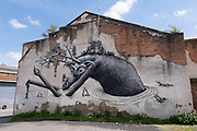Street art of a mythical horned figure saving people from drowning on the side of a building in Digbeth on 14th July 2021 in Birmingham, United Kingdom.