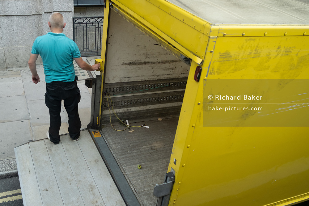 A delivery man presses the button to lower himself on the hydraulic tailgate of his now empty van that is parked on double-yellow lines in the London borough of Westminster, on 6th August 2020, in London, England.