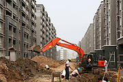 An excavator digs a ditch at the construction site of a new housing development  in Yangzhou, Jiangsu Province, China on 19 July 2012. While the Chinese government has tried various ways to cool down the property market, real estate prices have still seen a steady increase in recent years, proving hard for the country to move away from an investment driven economy.