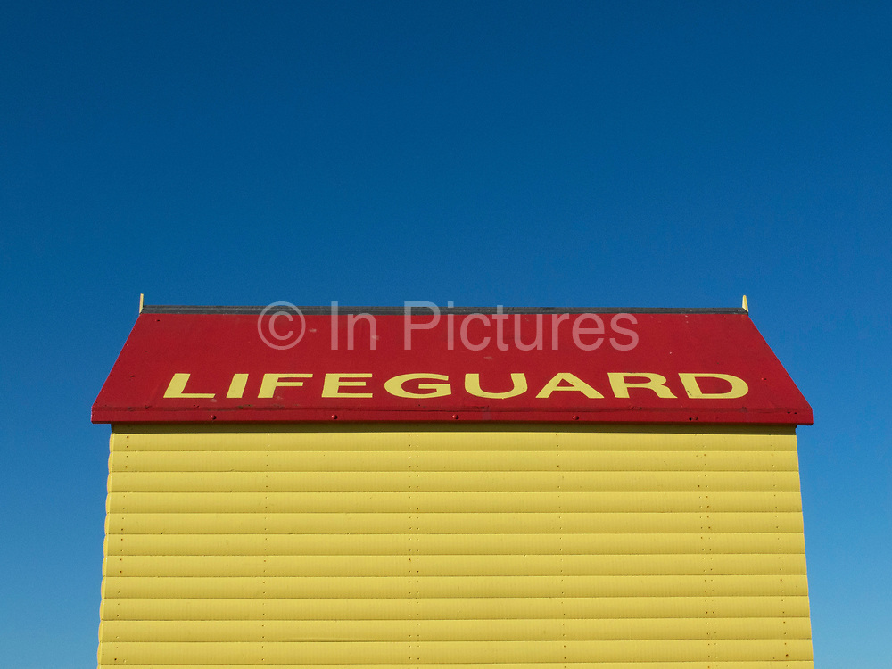 Yellow and red lifeguard hut by the sea on a blue sky day at Whitstable. Whitstable is a seaside town located on the north coast of Kent, in southeast England, UK. Whitstable is famous for its oysters. It's distinctive character is popular with tourists, and its maritime heritage is celebrated with the annual oyster festival. Freshly caught shellfish are available throughout the year at several seafood restaurants and pubs in the town.