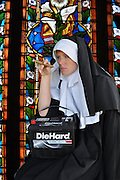 """Humorous photograph of a nun in a habit smoking a cigar in church and holding a Die Hard battery visually depicting the saying """"Bad habits die hard!"""""""