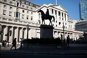 Statue of Wellington in silhouette in front of the Bank od England in the City of London, United Kingdom. The City, as it is known, is Londons historic financial district.