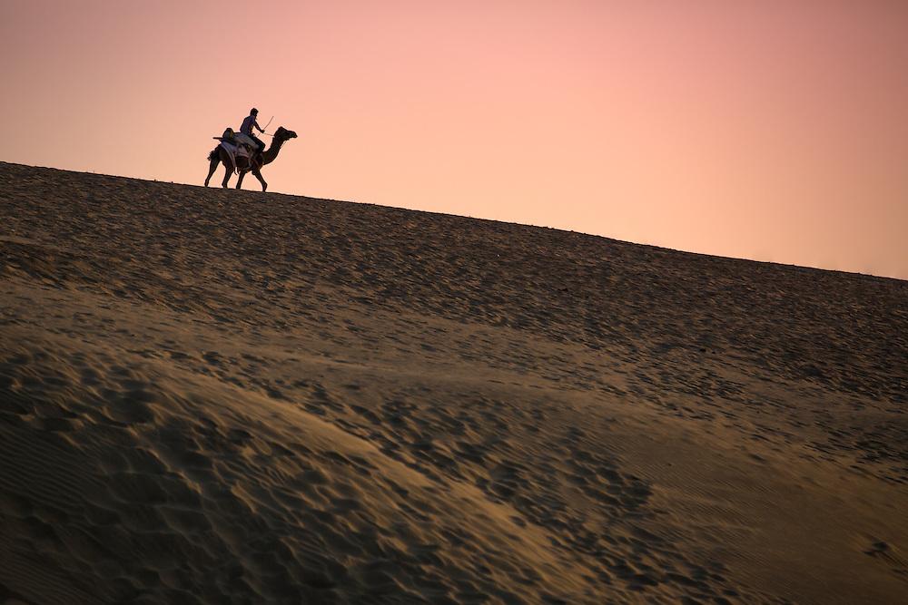 Night approaches over the sand of the Thar Desert near the golden city of Jaisalmer.