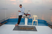 Writer, essayist and philosopher Alain de Botton leans against the wheel of a traditional dhoni boat in the Indian Ocean.