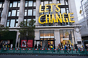 Massive sign reads 'Let's Change' outside Selfridges as Londoners await the imminent second coronavirus lockdown it's business as usual in the West End with large numbers of people, some wearing face masks and some not, coming to Oxford Street to go shopping on what will be the last weekend before a month-long total lockdown in the UK on 1st November 2020 in London, United Kingdom. The three tier system in the UK has not worked sufficiently, to suppress the virus, and there have have been calls by politicians for a 'circuit breaker' complete lockdown to be announced to help the growing spread of the Covid-19.
