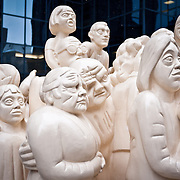 """""""The Illuminated Crowd"""" (1985) by English artist Raymond Mason. Installed outside a large office building in downtown Montreal, the sculpture carries the inscription: """"A crowd has gathered, facing a light, an illumination brought about by a fire, an event, an ideology--or an ideal. The strong light casts shadows, and as the lights toward the back and diminishes, the mood degenerates; rowdiness, disorder and violence occur, showing the fragile nature of man. Illumination, hope, involvement, hilarity, irritation, fear, illness, violence, murder and death--the flow of man's emotion through space."""""""