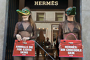 Two PETA supporters wearing Venetian crocodile masks pose outside the Hermès store in New Bond Street in protest against the luxury fashion houses use of exotic skins on 8th September 2021 in London, United Kingdom. PETAs campaign was launched following the release of video footage by Kindness Project showing crocodiles being mutilated, electrocuted, stabbed and shot on farms in Australia with ties to Hermès and PETA are calling on the fashion brand to cease using exotic skins for their products.