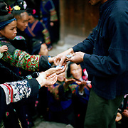 Villagers in the Long Skirt Miao village of Langde are handed money tickets for taking part in a music and dance performance in their village for Chinese tourists arriving by bus, Guizhou province, China