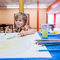 060513       Cable Hoover<br /> <br /> Ellis Ouellett paints colors into a tracing of his own silhouette during the first weekly Art Party at Hozho Center in Gallup Wednesday.