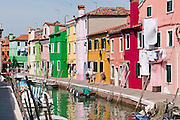 """Burano, known for knitted lacework, fishing, and colorfully painted houses, is a small archipelago of four islands linked by bridges in the Venetian Lagoon, northern Italy, Europe. Burano's traditional house colors are strictly regulated by government. The Romans may have been first to settle Burano. Romantic Venice, the """"City of Canals,"""" stretches across 117 small islands in the marshy Venetian Lagoon along the Adriatic Sea in northeast Italy, Europe. Venice and the Venetian Lagoon are honored on UNESCO's World Heritage List."""