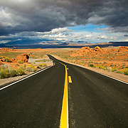 The iconic open, desert road is typical in Valley of Fire State Park. Nevada's oldest state park, it derives its name from red sandstone formations, formed from great shifting sand dunes during the age of dinosaurs. These features, which are the centerpiece of the park's attractions, often appear to be on fire when reflecting the sun's rays.