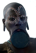 Young Woman with clay lip plate and face painted, Mursi Tribe, Mago National Park, Lower Omo Valley, Ethiopia, portrait, person, one, tribes, tribal, indigenous, peoples, Southern, ethnic, rural, local, traditional, culture, primitive,