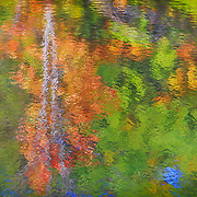 Reflections of autumn foliage in moving surface of garden pond on a windy fall day. Painted effects blended with original photograph.