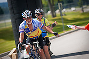 Tandem bicyclists Jack and Gaynelle Stamm of St. Regis, Montana gratefully reach for water from a volunteer at the finish line of the Blue Cruise. The Stamms were the first finishers in the thirty-two mile route which started and finished at Woodland Middle School on Saturday.