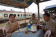 ROYAL CAMBODIAN RAILWAYS. The journey from Phnom Penh to Battambang is the last working route. A passenger train, operates only at weekends. A Czech made diesel locomotive, leaves the capital Saturday morning, arriving in Battambang 22 hours later in the dead of night, and returns on Sunday. Max speed is about 30kmh, often slower due to the track's terrible condition. Carriages are dilapidated, with holes in the floor and only spaces for windows. Passengers sit or sleep on hardwood bench seats, hammocks, or on the floor of cargo carriages. The drivers, controllers & guards add to their small monthly pay by charging for local passengers and cargo; from motor bikes and local produce to timber loaded aboard at the 30 stations along the route. This together with other trains and farm vehicles further slows the journey. In rural areas, the track is a lifeline, and used for local transport on 'bamboo trains' powered by belt-motors, or pushcarts. Boom towns, with a 'goldrush mentality' near the rapidly depleted rainforest, are a hive of activity, with logging as their resource, where children workers even gamble away their earnings on cardgames. In the city, the railway has a life of its own, where people live and work nearby or on the track itself. Market stalls, restaurants, chairs and tables, are removed only briefly, when the infrequent train passes!///Ticket collectors having breakfast ay Battambang before the return journey