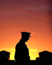 © Licensed to London News Pictures. <br /> 16/12/2014. <br /> <br /> Hartlepool, United Kingdom<br /> <br /> Soldiers stand to attention at sunrise during a memorial event to commemorate the bombardment of Hartlepool by German warships during World War One. During the bombardment 130 civilians were killed and more than 500 were wounded. The Headland's Heugh Gun Battery returned fire in what was the only battle to be fought on British soil during World War One, and one of the Battery's soldiers, Theo Jones of the Durham Light Infantry, became the first British soldier to be killed by enemy action on home ground in the war.<br /> <br /> Photo credit : Ian Forsyth/LNP