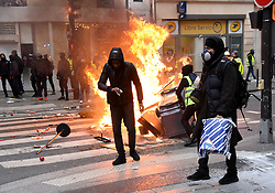 "Police clash on Saturday december 8, 2018 in Paris, France, with protesters staging a fourth weekend of ""gilets jaunes,"" or ""yellow vest,"" demonstrations against the government of President Macron. Officers fired rubber bullets and hundreds of canisters of tear gas at the demonstrators, some of whom had set vehicles on fire. Interior Minister Christophe Castaner said 135 people were wounded in Saturday's protests across France, including 17 police officers. Castaner said 1,385 people were taken in for questioning and 974 were in custody. Two photographers from the newspaper Le Parisien were hit by projectiles. One was taken to hospital as dusk drew near in a city still in shock from last weekend's riots -- the worst to hit the French capital in decades. Photo by Alain Apaydin/ABACAPRESS.COM"