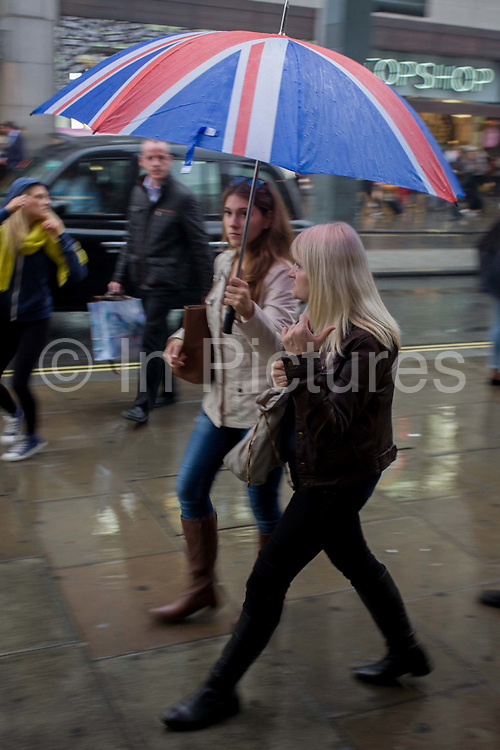 Londoners walk along central London's Oxford Street during autumnal rain. Holding a Union jack umbrella, two women walk and talk in the rain shower, on a damp pavement in the capital's West End - a centre for retail whose business is is under threat by covered malls elsewhere. The crowds have flocked to this old street, once the route for criminals towards the Tyburn gallows.
