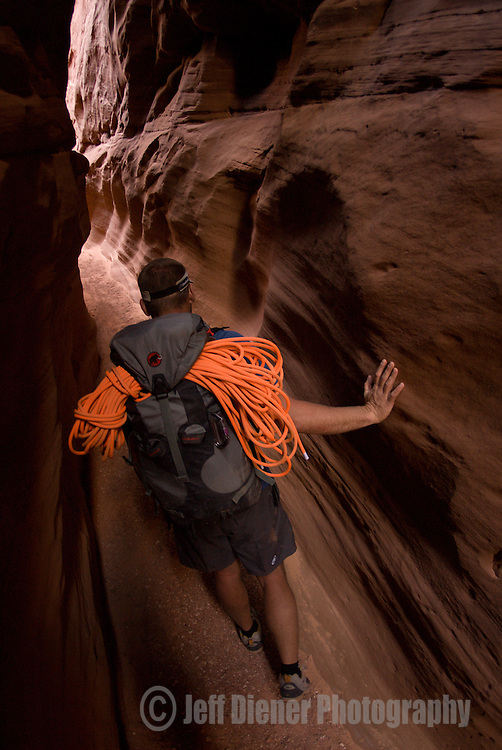 A young man hikes Blue John Canyon in the Robbers Roost Canyon area of Utah.