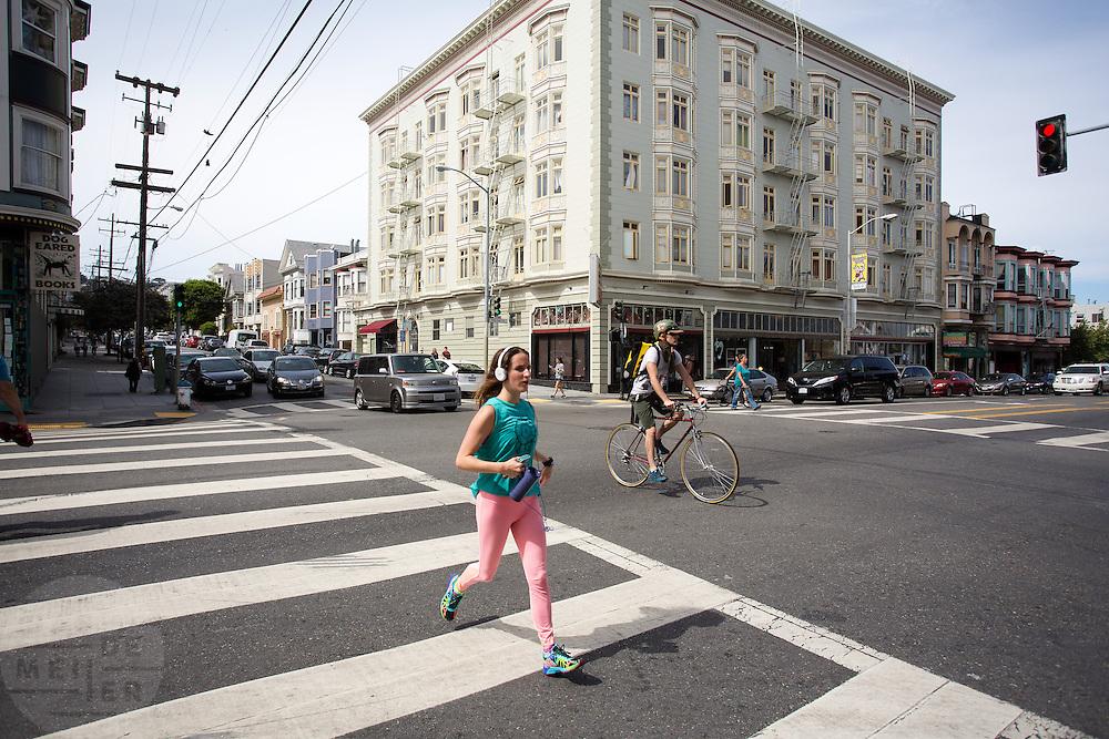 Fietsers en hardloopster in San Francisco. De Amerikaanse stad San Francisco aan de westkust is een van de grootste steden in Amerika en kenmerkt zich door de steile heuvels in de stad. Ondanks de heuvels wordt er steeds meer gefietst in de stad.<br /> <br /> Cyclists in San Francisco. The US city of San Francisco on the west coast is one of the largest cities in America and is characterized by the steep hills in the city. Despite the hills more and more people cycle.