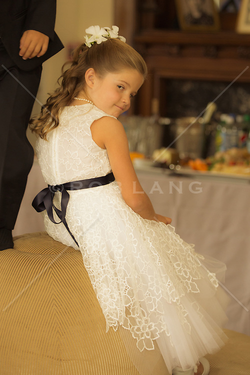 little girl in a formal dress seated at a wedding reception