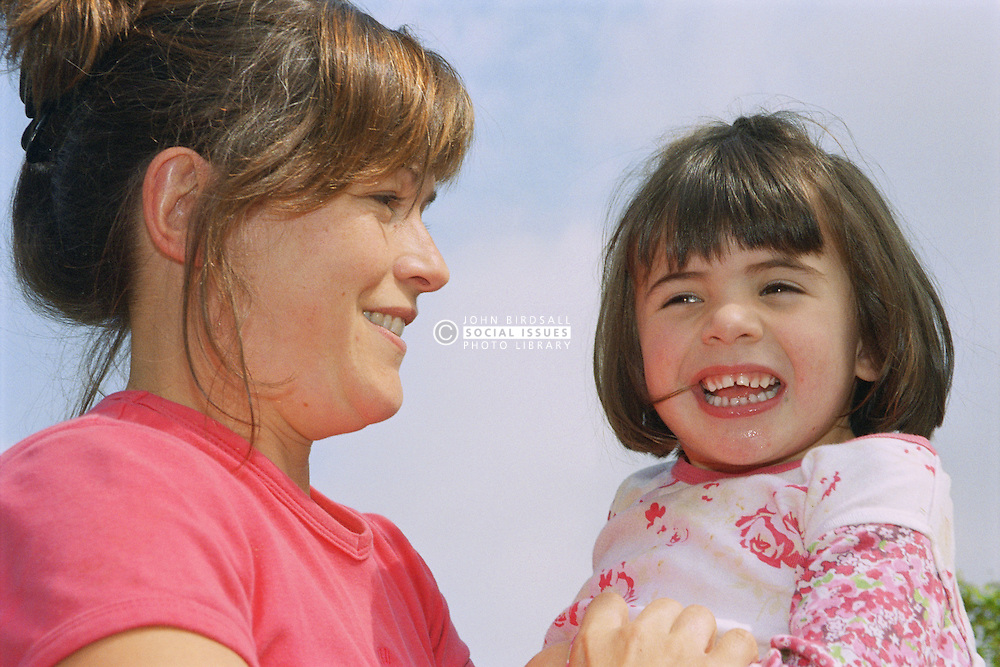 Young girl with autism being held and tickled by mother,