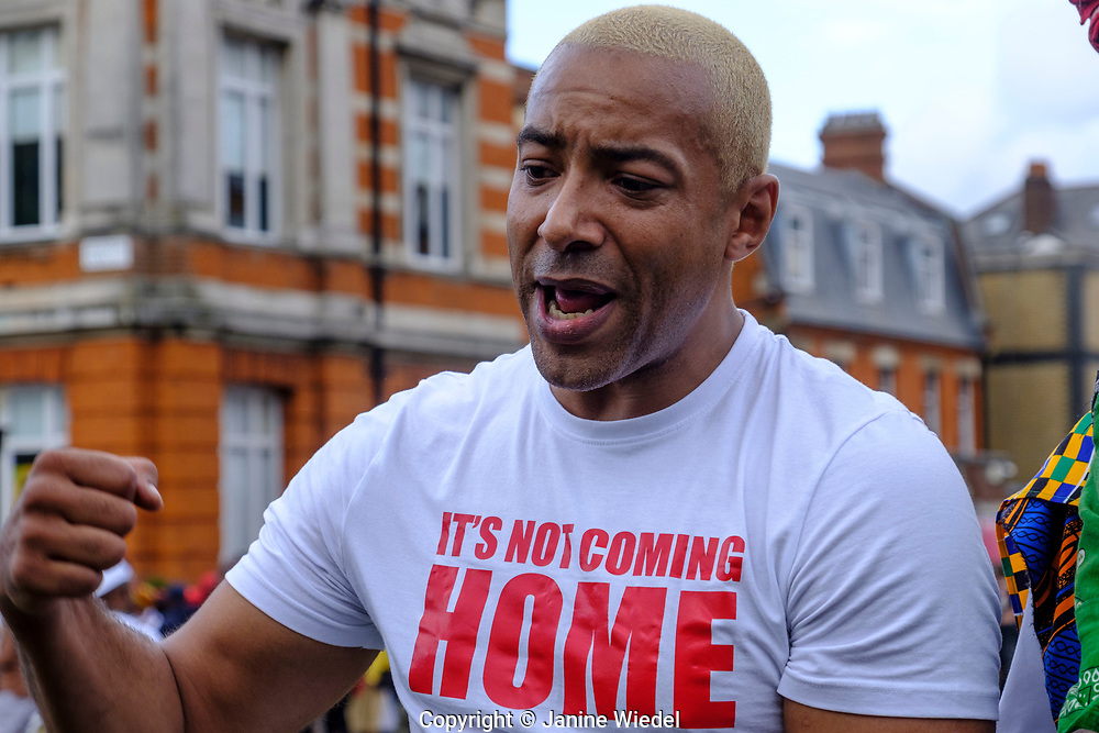 Musician / songwriter  Koba Kane with raised fist at Reparations Revolution on Emancipation Day 2021. Windrush Square Brixton London