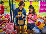 16 NOVEMBER 2013 - BANGKOK, THAILAND:  Teenagers send SMS messages to their friends before playing a darts game at the Wat Saket temple fair. Wat Saket is on a man-made hill in the historic section of Bangkok. The temple has golden spire that is 260 feet high which was the highest point in Bangkok for more than 100 years. The temple construction began in the 1800s in the reign of King Rama III and was completed in the reign of King Rama IV. The annual temple fair is held on the 12th lunar month, for nine days around the November full moon. During the fair a red cloth (reminiscent of a monk's robe) is placed around the Golden Mount while the temple grounds hosts Thai traditional theatre, food stalls and traditional shows.   PHOTO BY JACK KURTZ