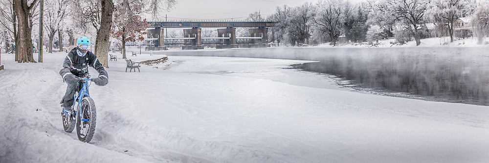 Biting cold raises steam on the soon-to-be frozen river and nearby trees are flocked with ice.  But, arctic conditions are not a barrier for this bicyclist.