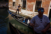A gondola ride in a narrow canal in Venice, Italy. The first mention ever of an Italian gondola was in Venice in 1094 and, of course, there have been gondoliers as long as there have been gondolas - so it's one of the oldest professions in the world. Until August 2010, there had never been a single woman gondolier in Venice as licences were always passed down to male family members. Current prices (2015) is 80 Euros for a 40-minute journey (earning them approx 130,000 Euros a year) along the waterways of this old city but rarely do gondoliers wear their straw hat.