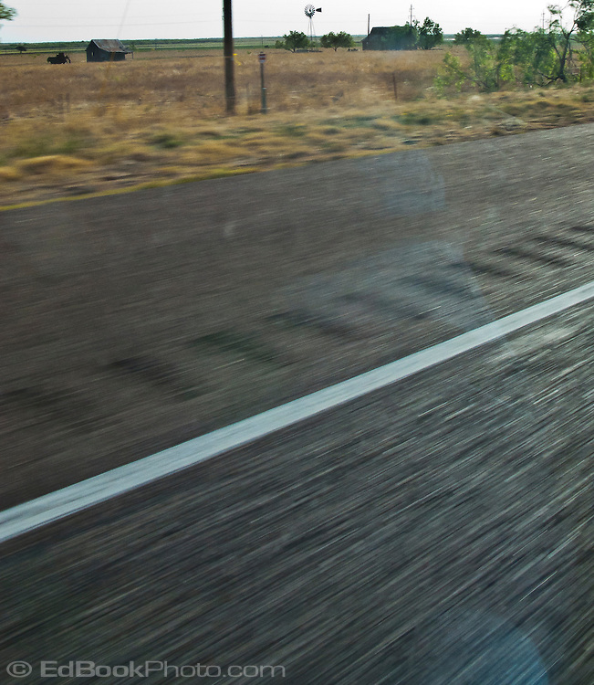 Pavement streaks by along a highway in west Texas with a couple small farm buildings and windmill.  flat land