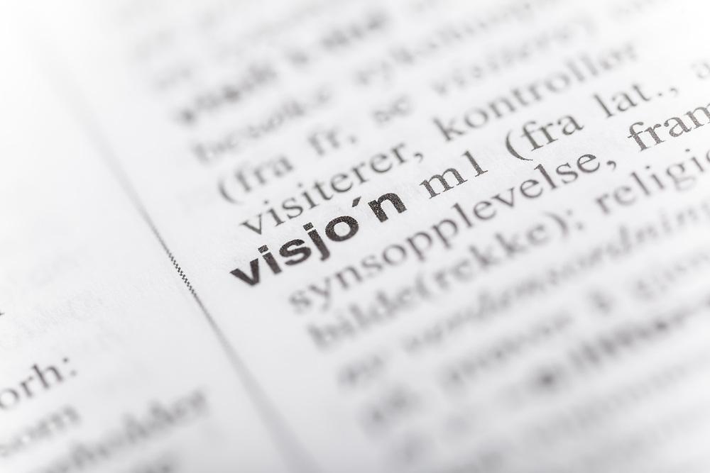 Selektiv fokus på ordet «visjon» i ordboka.
