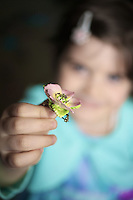 Young girl holding up and showing a ceramic flower broach to camera.