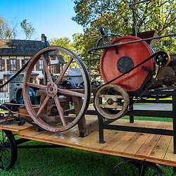 Lancaster, PA - October 12, 2012: A farm machine with wheels, pulleys, and belts mounted on a wagon is on display at the Landis Valley Village & Farm Museum in Lancaster County, PA.