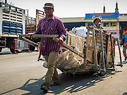 """15 FEBRUARY 2016 - ARANYAPRATHET, SA KAEO, THAILAND: A Cambodian porter in Aranyaprathet brings a load of textiles from the Cambodian side of the border into Thailand. Thais selling bottled water in the border town of Aranyaprathet, opposite Poipet, Cambodia, have reported a surge in sales recently. Cambodian officials told their Thai counterparts that because of the 2016 drought, which is affecting Thailand and Cambodia, there have been spot shortages of drinking water near the Thai-Cambodian and that """"water shortages in Cambodia had prompted people to hoard drinking water from Thailand.""""     PHOTO BY JACK KURTZ"""
