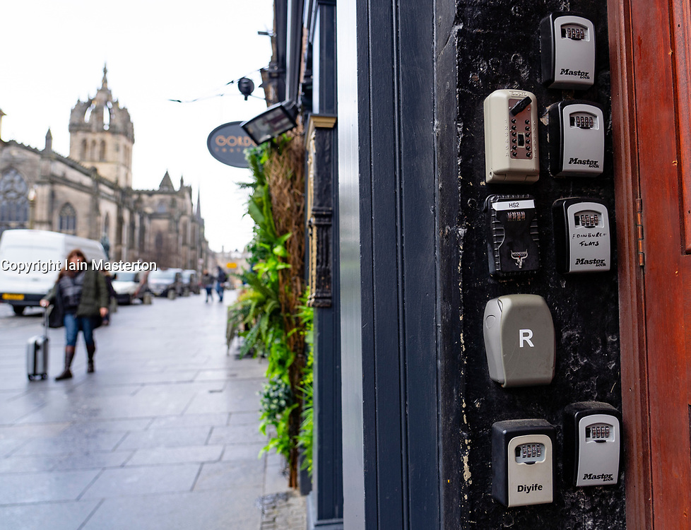 Many key safes used for AirbnB type short-term letting beside apartment building door on Royal Mile in Edinburgh Old Town, Scotland, UK