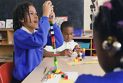 Primary school children using unilink blocks in practical maths lesson,