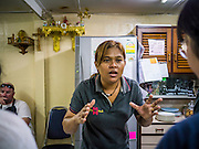"""29 MARCH 2013 - BANGKOK, THAILAND: Saiyuud Diwong """"Poo""""  talks to her students about the flavor combinations in Thai food in her cooking school. On the wall in the school she has a shrine to the Ganesha, a Hindu deity, a Christian cross and a Buddha.   PHOTO BY JACK KURTZ"""