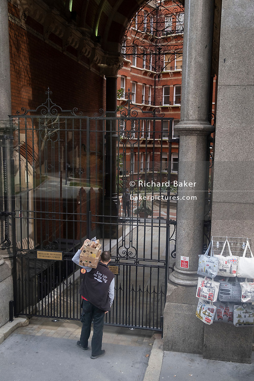 A delivery man from Riverford Organic Farmers waits outside the gated Victorian-era Artillery Mansions, an address on Victoria Street in Victoria SW1, Westminster, during the second wave of the Coronavirus pandemic, on 20th October 2020, in London, England.