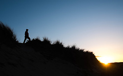 © Licensed to London News Pictures. <br /> 08/03/2015. <br /> <br /> South Gare, Redcar, United Kingdom<br /> <br /> A woman stands in the dunes and watches the sun set at South Gare near Redcar.<br /> <br /> Photo credit : Ian Forsyth/LNP