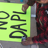 """Reuben Begay paints """"No DAPL"""" on a sign during a sing making workshop by the Red Nation at the Navajo Nation Museum in Window Rock Friday. No DAPL refers to the Dakota Access Pipeline that the Sioux tribe is currently protesting by blocking the construction. On Friday a Federal judge denies the request by Standing Rock to halt the pipeline construction, however the U.S. Army Corps of Engineers moved to suspend construction despite the Judge's ruling."""