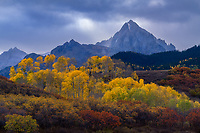 Peak fall color and moody skies over Mt Sneffels in Colorado, USA