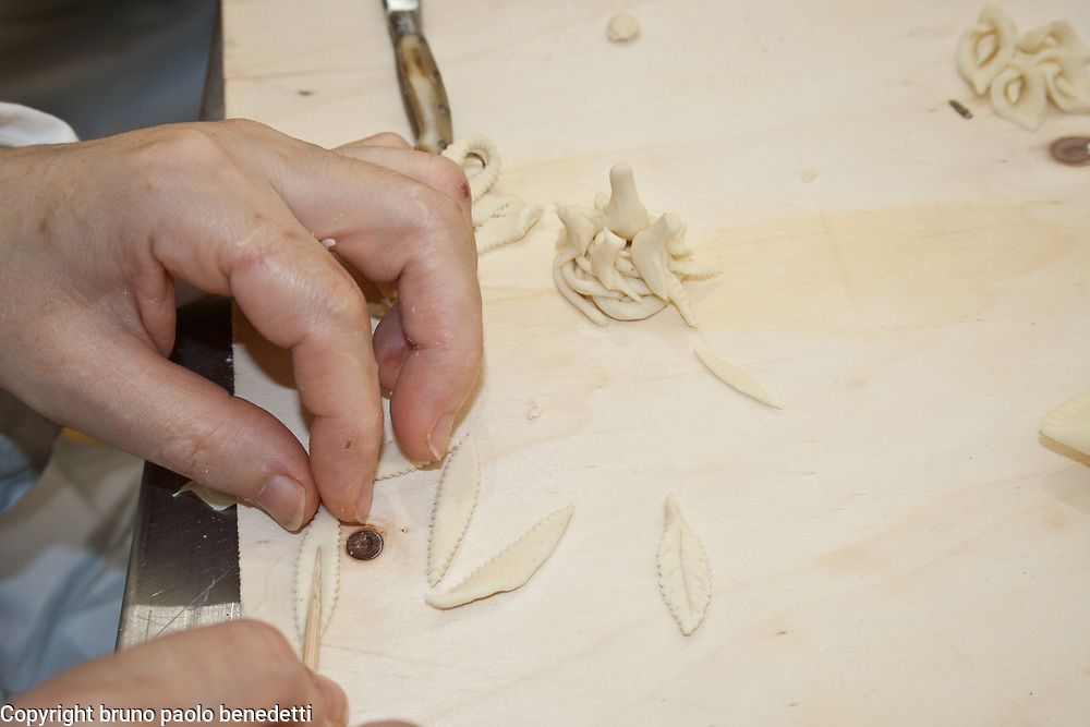 making bread decorations using a sharp tool for the interior of a leaf shape.