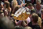 Nederland, Nijmegen, 16-7-2014 Recreatie, ontspanning, cultuur, dans, theater en muziek in de binnenstad tijdens de zomerfeesten. Hier op het volle Koningsplein waar de band Beethoven optrad. Een van de tientallen feestlocaties in de stad. Onlosmakelijk met de vierdaagse, 4daagse, zijn in Nijmegen de vierdaagse feesten, de zomerfeesten. talrijke podia staat een keur aan artiesten, voor elk wat wils. Een week lang elke avond komen tegen de honderdduizend bezoekers naar de stad. De politie heeft inmiddels grote ervaring met het spreiden van de mensen, het zgn. crowd control.De vierdaagsefeesten zijn het grootste evenement van Nederland en verbonden met de wandelvierdaagse. Bier,drinken,alkohol,alcohol,drank,blad, dienblad met volle glazen.Foto: Flip Franssen/Hollandse Hoogte