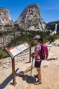 Hiker reading interpretive sign on the John Muir Trail below Nevada Fall , Yosemite National Park, California USA