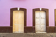 A purple wall and wooden doors in Angangueo, Michoacan, Mexico. Angangueo is a tiny, remote mountain town and the entry point to the Sierra Chincua Monarch Butterfly Sanctuary.