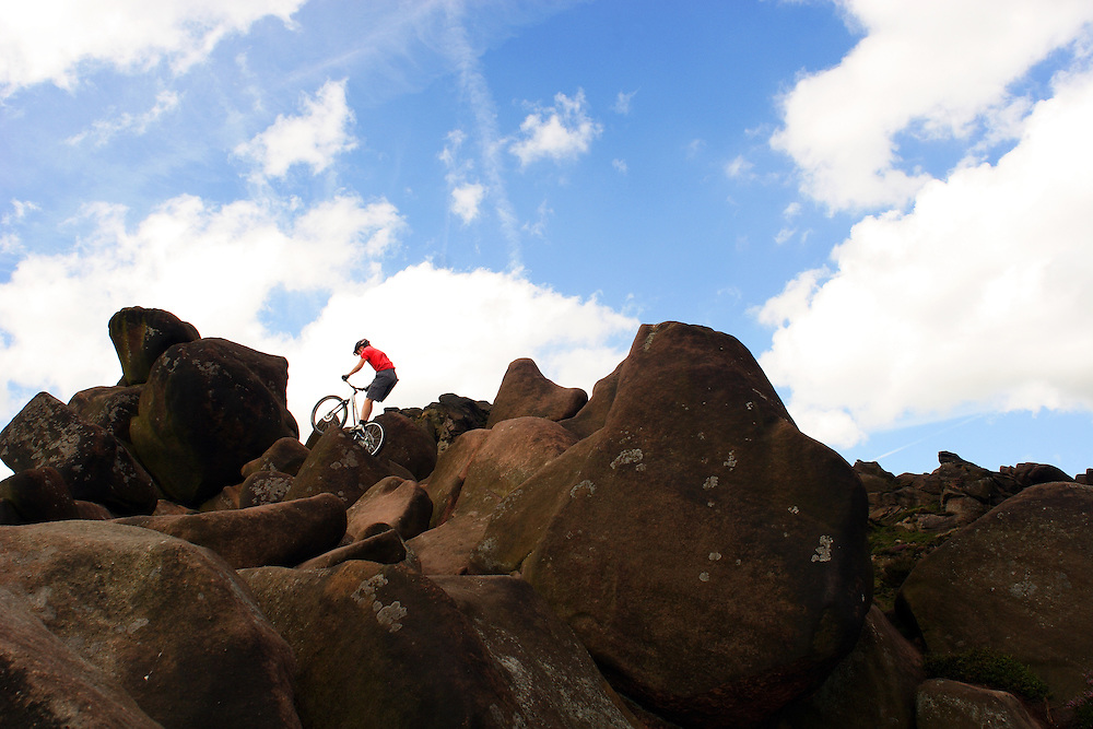A trails bike ride jumps rock at the Roaches, Staffordshire, England, United Kingdom, Europe.